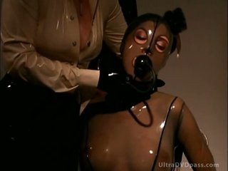 Blond Dominatrix Makes Breasty Submissive Brunette Wear Suffocating Latex Suit