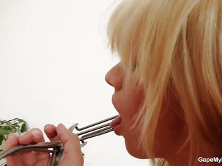 sweet blonde gaping her shaved vagina with a metal speculum