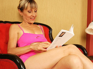 Blonde mature drab in pink underwear is posing on the large bed